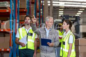 Warehouse manager and workers discussing with clipboard