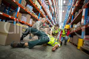 Worker fallen down while carrying cardboard boxes