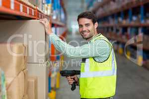 Portrait of smiling warehouse worker scanning box
