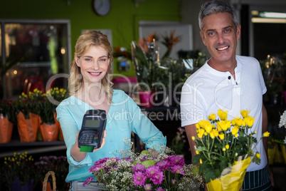 Smiling florist showing credit card terminal in flower shop