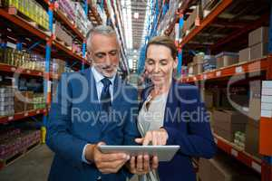 Warehouse manager and client discussing over digital tablet