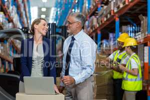 Warehouse manager and client interacting over laptop