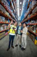 Warehouse team discussing with digital tablet