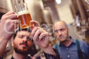 Owner inspecting beer in mug