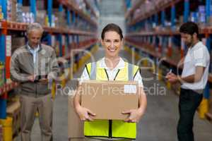 Female worker holding cardboxes while colleague working in background