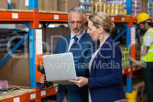 Warehouse manager and client using laptop
