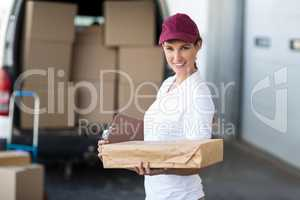 Portrait of delivery woman holding a clipboard and parcel