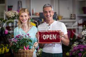 Florists holding open sign placard and flower basket in flower shop