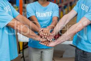 Mid section of volunteers putting hands together