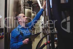 Male manufacturer examining machinery