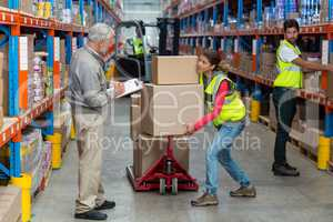 Warehouse manager noting on clipboard while female worker carrying cardboard boxes