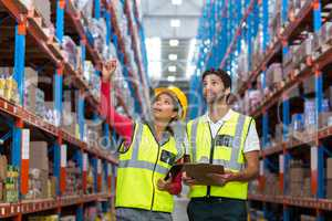 Warehouse workers discussing with clipboard while working