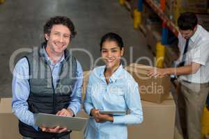 Warehouse workers using laptop and digital tablet