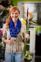 Smiling female florist trimming flower stem