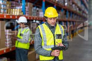Warehouse worker using barcode scanner machine