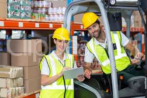 Male and female worker discussing over clipboard