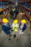 Warehouse manager using digital tablet with client and female worker