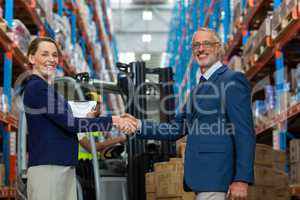 Warehouse manager shaking hands with client
