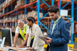 Warehouse managers and worker working together