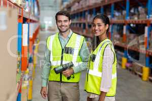 Portrait of smiling warehouse workers scanning box