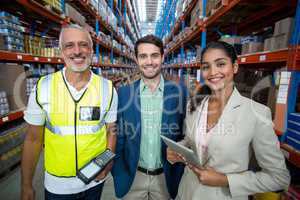 Portrait of warehouse team standing with digital tablet and barcode scanner