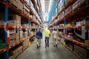 Warehouse team discussing while walking in warehouse