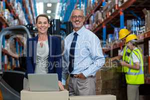 Portrait of warehouse manager and client standing with laptop