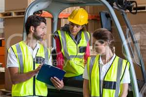 Warehouse workers talking with forklift driver