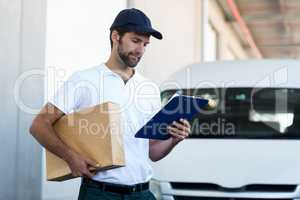 Delivery man holding a parcel and looking at clipboard