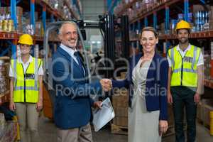 Portrait of warehouse manager shaking hands with client