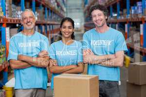 Portrait of three happy volunteers standing with arms crossed