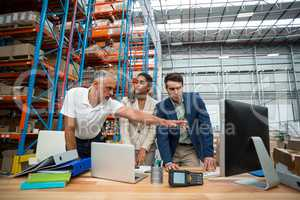 Warehouse managers and worker discussing with computer