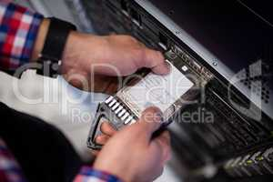 Technician inserting a hard disk drive into a blade server