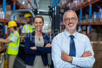 Portrait of warehouse manager and client smiling with arms crossed