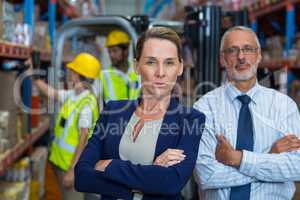 Portrait of warehouse manager and client standing with arms crossed