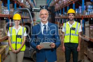Portrait of warehouse manager and co-workers standing with clipboard