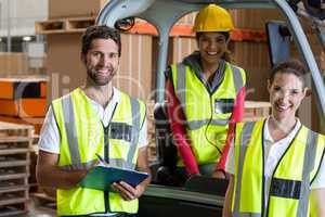 Portrait of warehouse workers and forklift driver