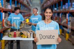 Portrait of happy volunteer holding sign boards with message