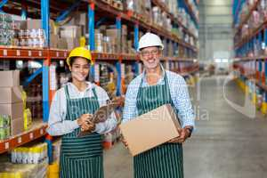 Portrait of warehouse workers standing with clipboard and cardboard boxes