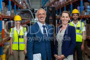 Portrait of warehouse manager standing with client