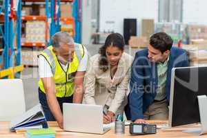 Warehouse managers and worker discussing with laptop