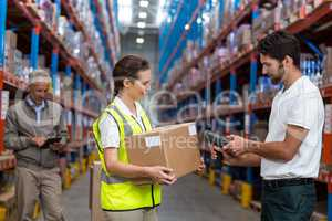 Female worker holding cardboard box while male worker scanning barcode