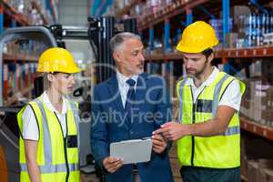 Warehouse manager and co-workers discussing over clipboard