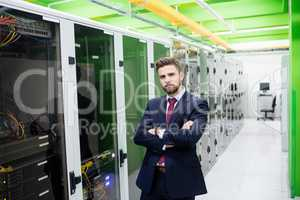 Technician standing with arms crossed in a server room