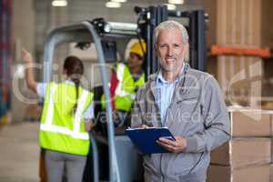 Portrait of warehouse manager holding a clipboard