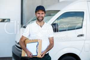 Portrait of delivery man holding parcels and clipboard