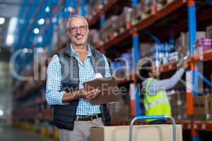 Warehouse manager smiling and holding clipboard