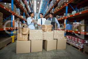 Warehouse workers and manager discussing with laptop