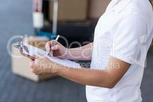 Mid section of delivery woman writing on clipboard