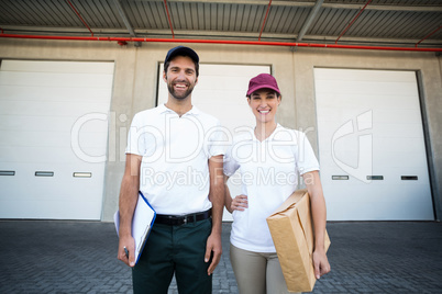 Portrait of delivery man and woman standing with clipboard and parcel